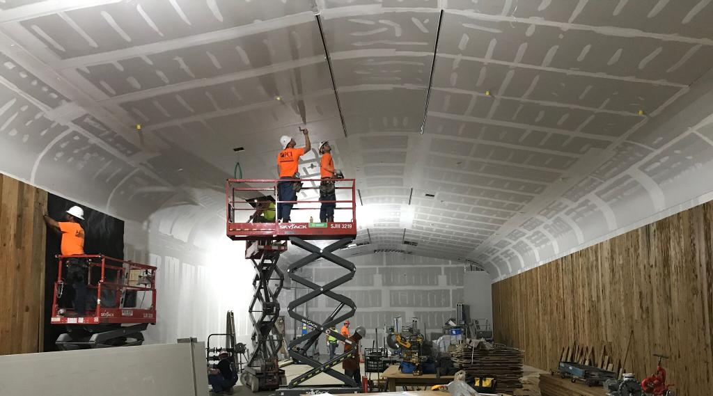 A PCI crew finishing a sloped drywall ceiling