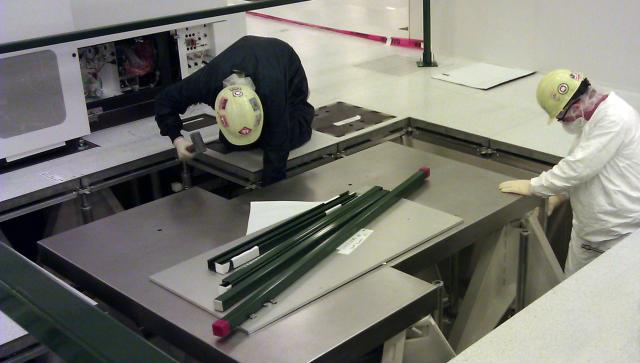 A crew installs specialty tools in a cleanroom facility